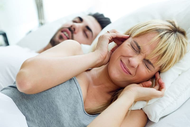 wife lying while covering ears annoyed by husband snoring sleeping beside her