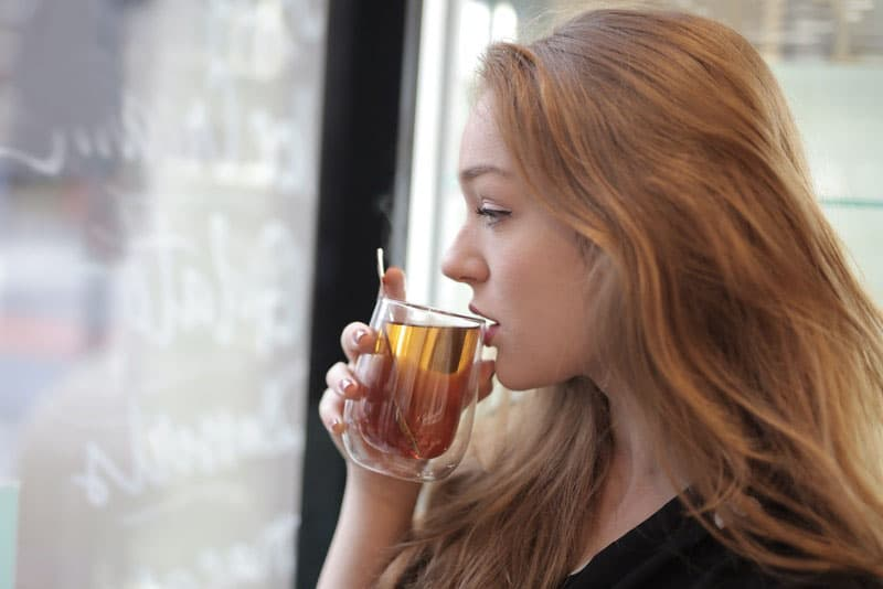woman about to drink tea from a cup near the windows