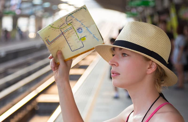 woman bringing a map wearing a hat standing along a subway