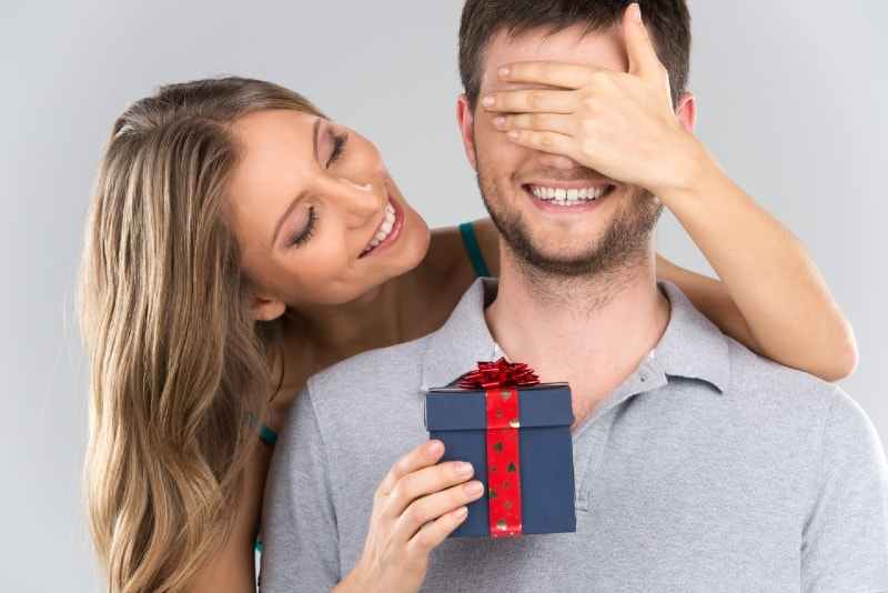 woman covering man's eyes while giving him gift