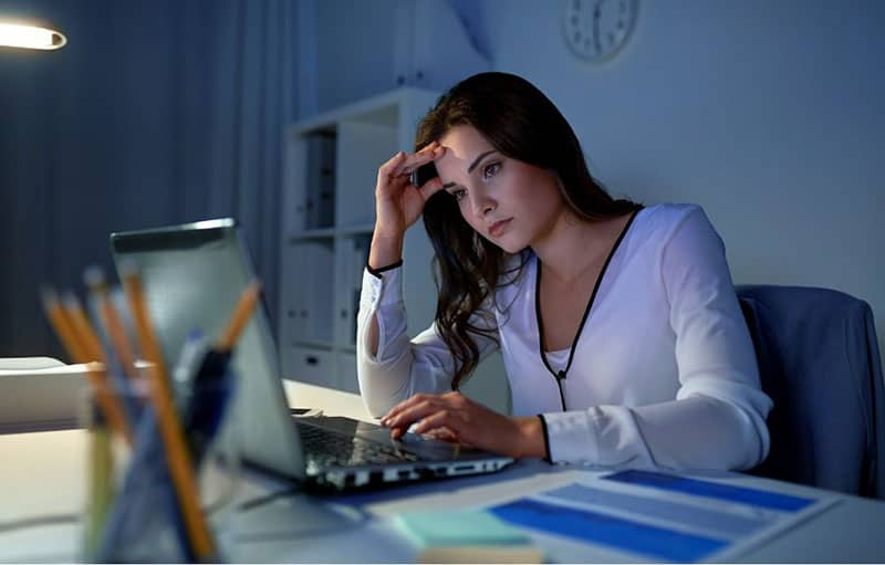 woman facing the laptop while thinking deeply inside office setup