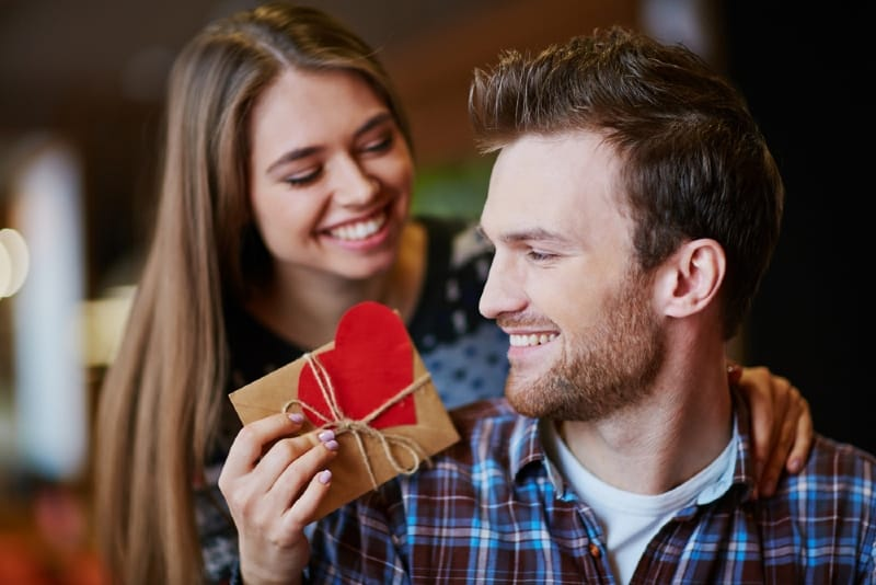 smiling woman giving gift to man