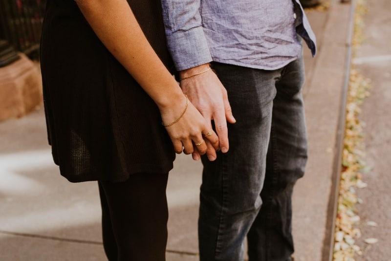 woman holding man's hand on the sidewalk