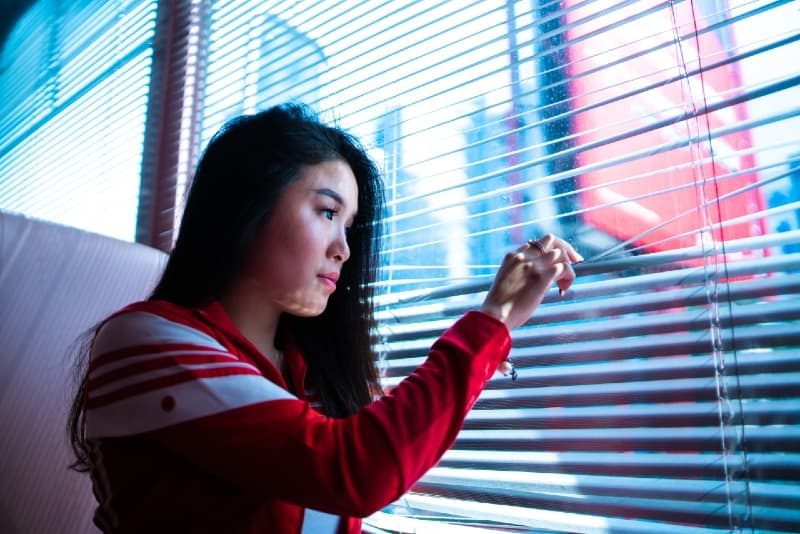 woman holding on window blinds during daytime