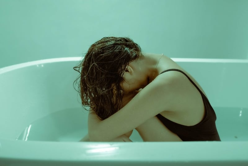 woman holding her knees while sitting in bathtub