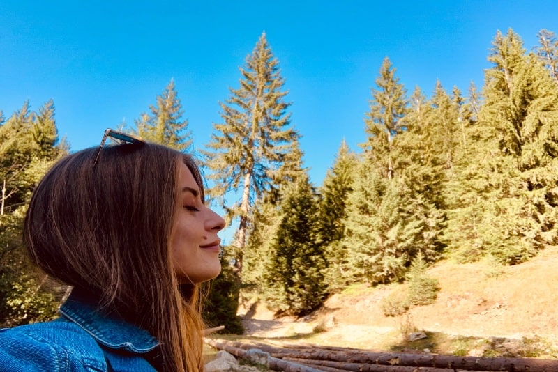 woman with eyes closed standing in forest