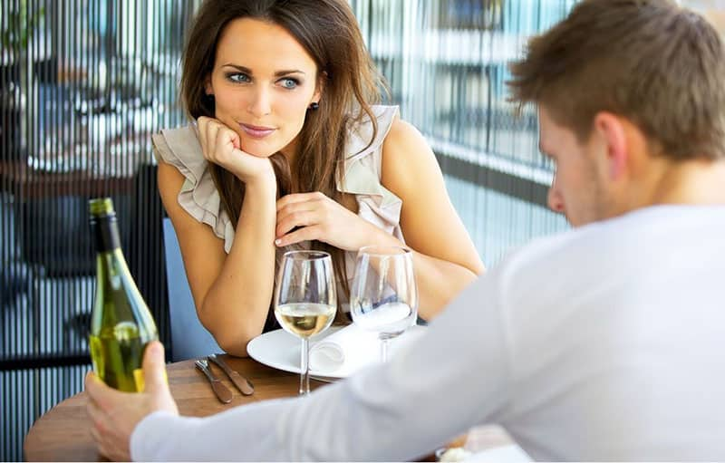 woman in love listening to the man talking about the wine in their table