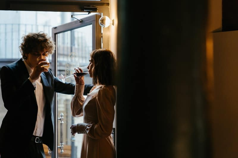 woman in white coat drinking wine dating with a man near the door