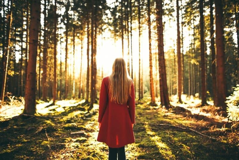 woman in red coat standing in woods