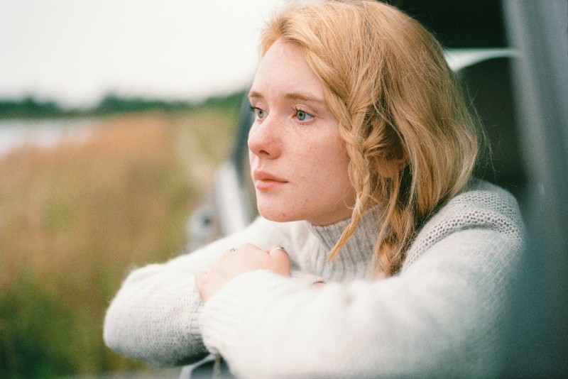 woman in white sweater leaning on car window