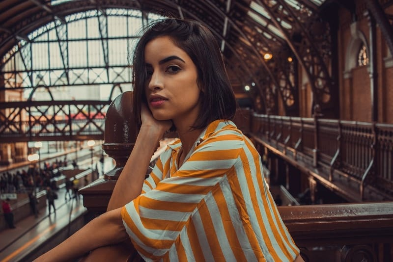 woman in striped top leaning on railings