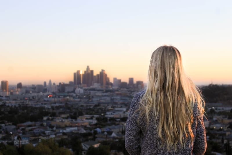 blonde woman looking at city during sunset
