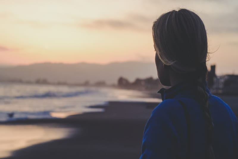 woman in blue jacket looking at sea during sunrise