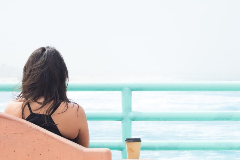 woman looking at sea while sitting outdoor