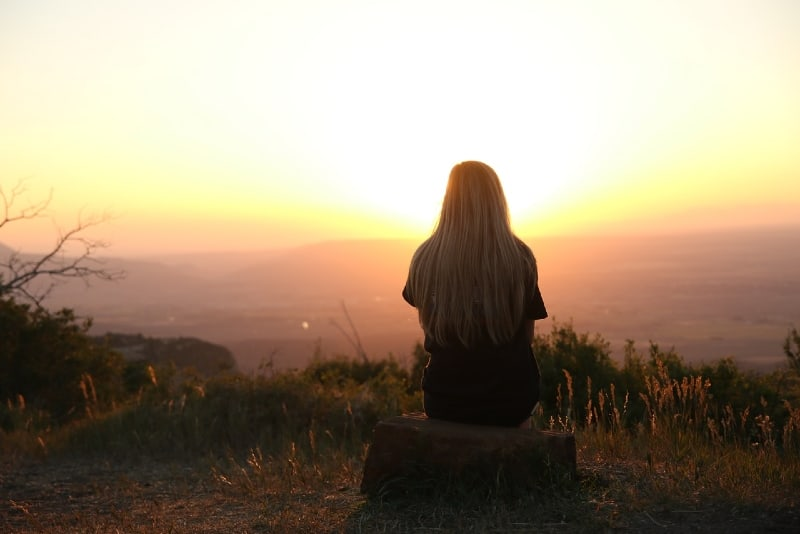 blonde woman looking at sunset while sitting on rock