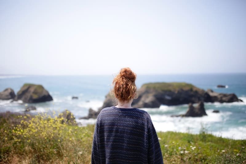 woman in printed sweater looking at water