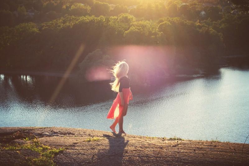 blonde woman in black top looking at water