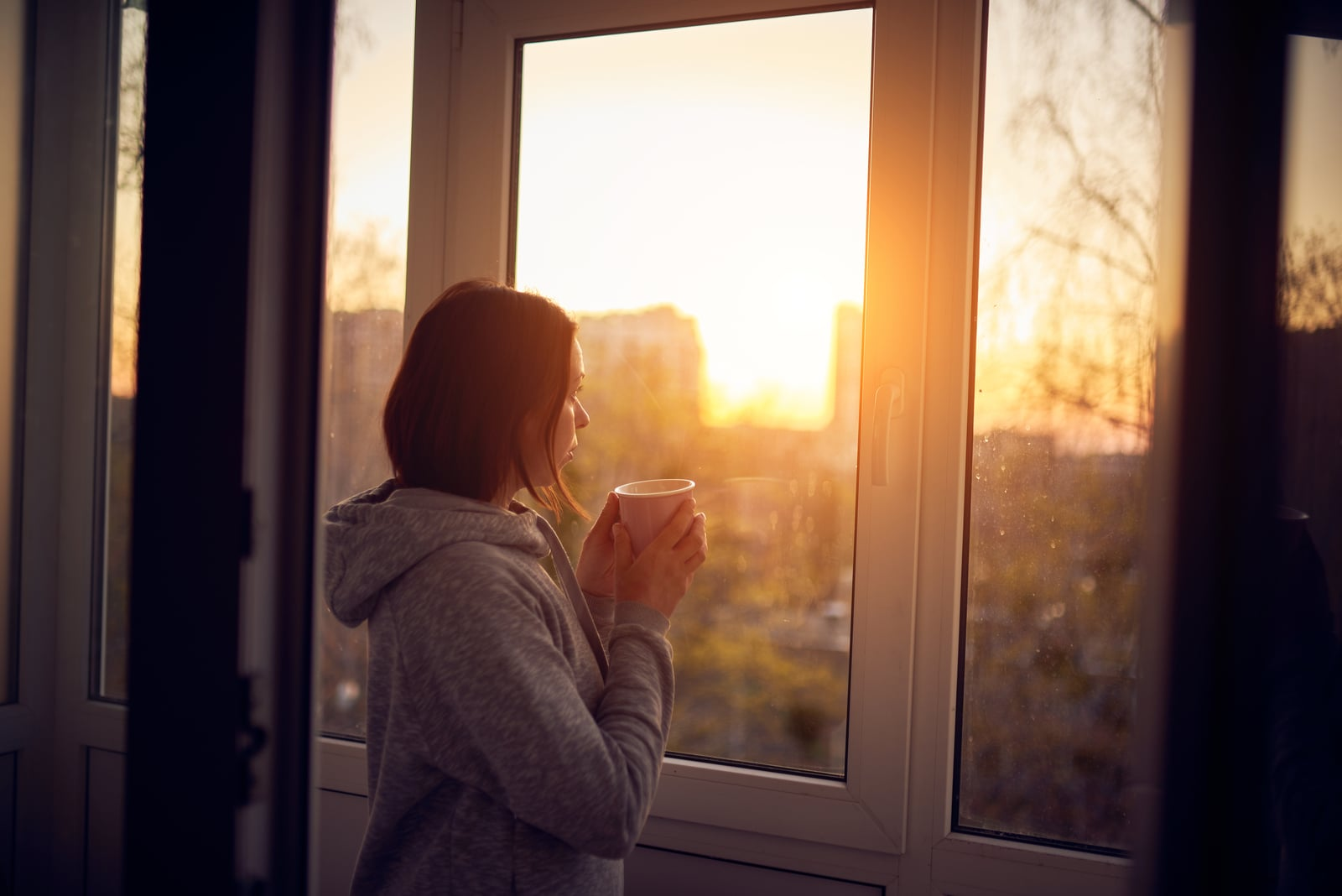 woman holding cup of tea and looking out of window