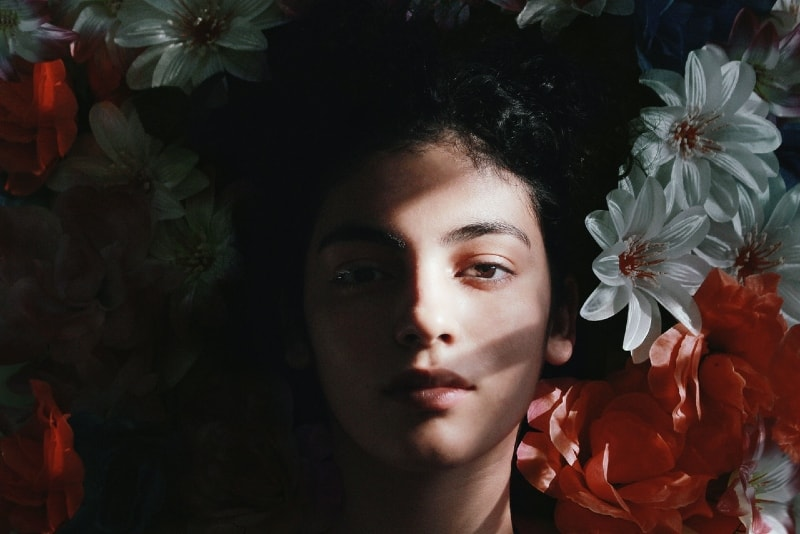 woman lying on white and red flowers