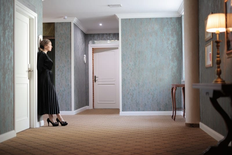 woman near the door standing wearing black dress and shoes