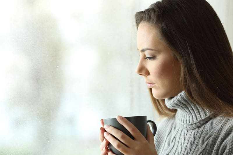 woman near the glass window drinking a cup of coffee while thinking