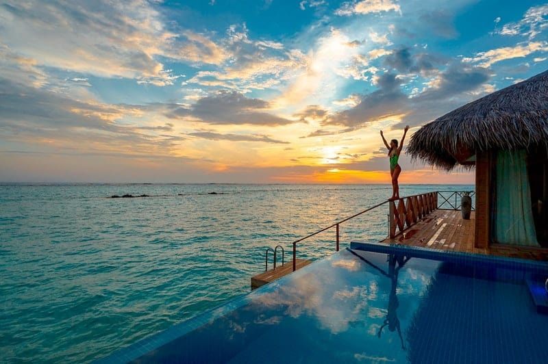 woman on bathing suit standing near the infinity pool and beach house during sunset