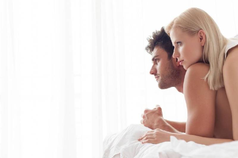 woman on top of the man lying on the bed facing at the same direction