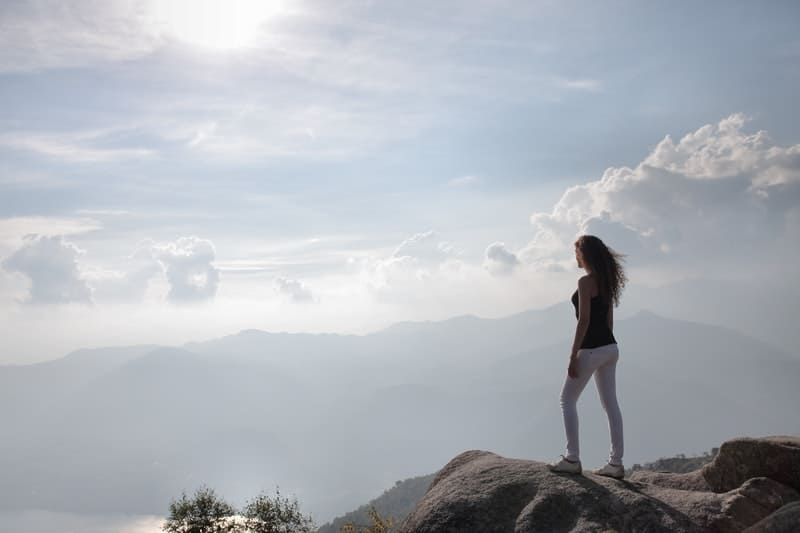 woman on top of the mountain with sun shining, woman wearing white jeans