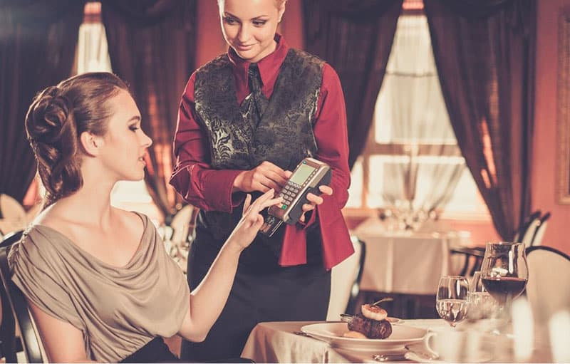 woman paying bill with a card in a restaurant