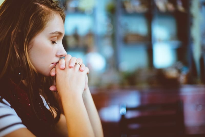 woman with eyes closed praying
