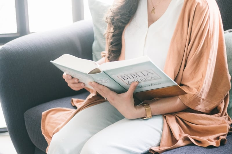 woman in brown robe reading book