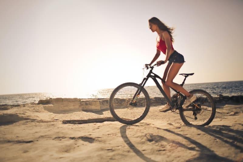 woman in red top riding bike near sea