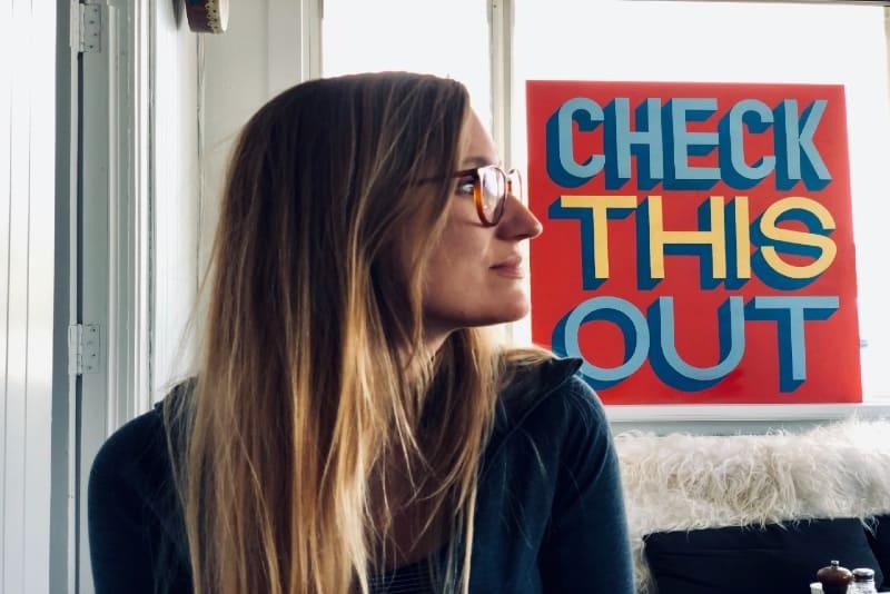 woman with eyeglasses sitting indoor