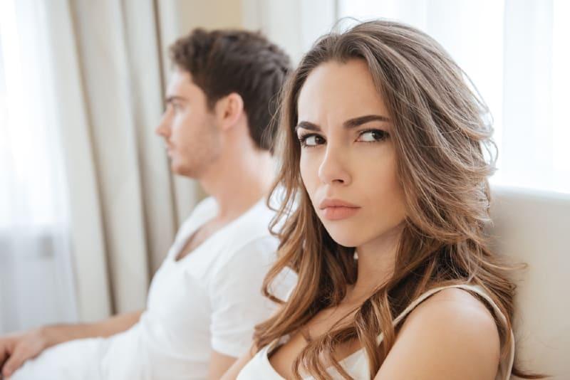 angry woman sitting on sofa near man