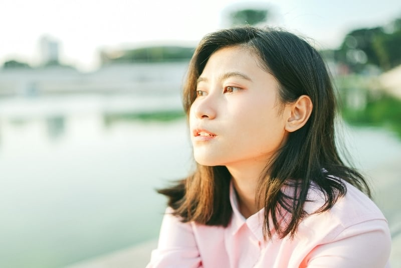 woman sitting near water during daytime