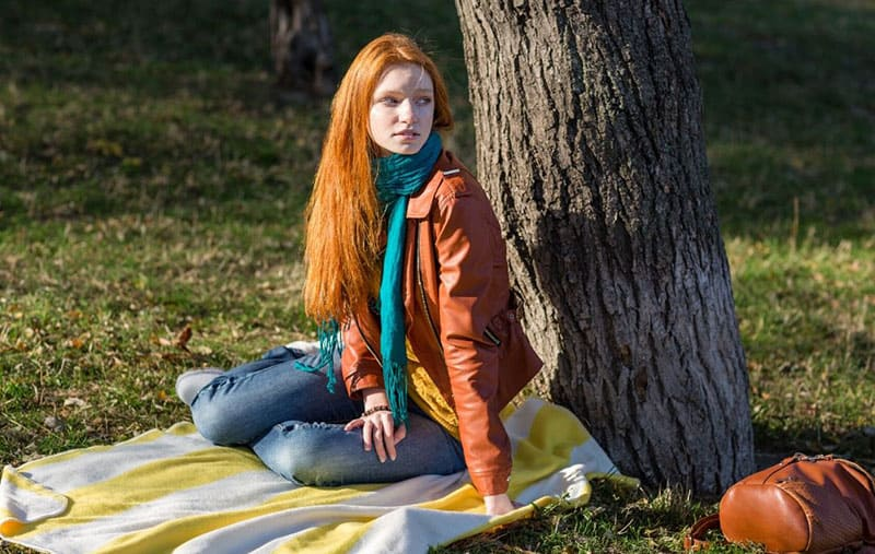 woman sitting on picnic mat under a tree looking far and wearing brown jacket