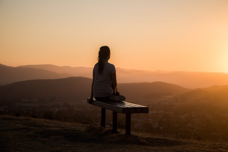 woman sitting on bench looking at mountain during sunset