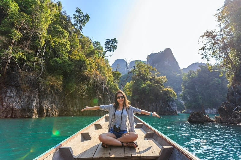 woman sitting on boat sailing thru a body of water in the middle of big rock cliffs spreading her arms with happiness
