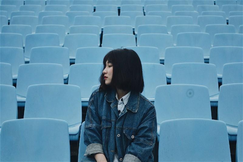 woman in denim jacket sitting on blue chair