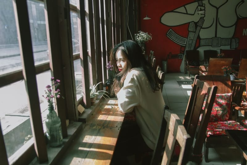 sad woman sitting on chair leaning on table near window