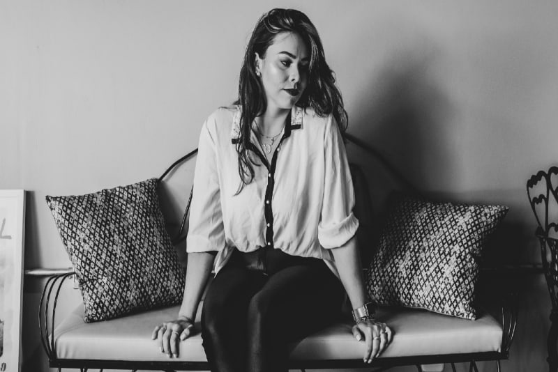 sad woman in white shirt sitting on couch