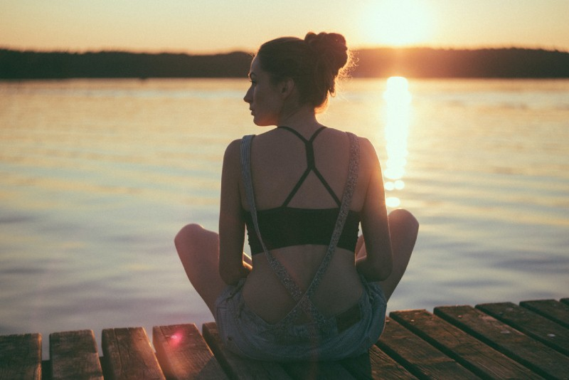 woman sitting on dock during sunset