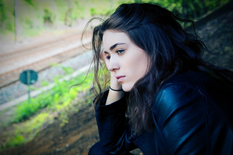 woman in black jacket sitting on ground