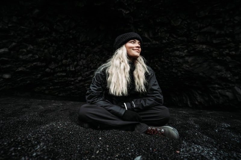 blonde woman in black jacket sitting on ground