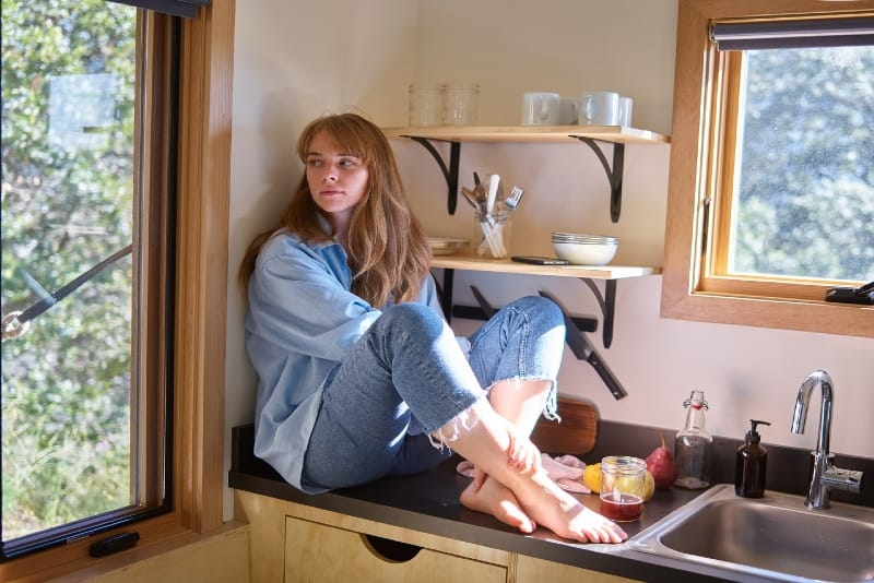 woman in blue shirt sitting on kitchen counter