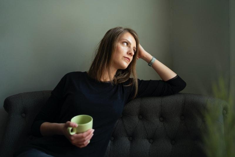 woman holding mug and sitting on black sofa