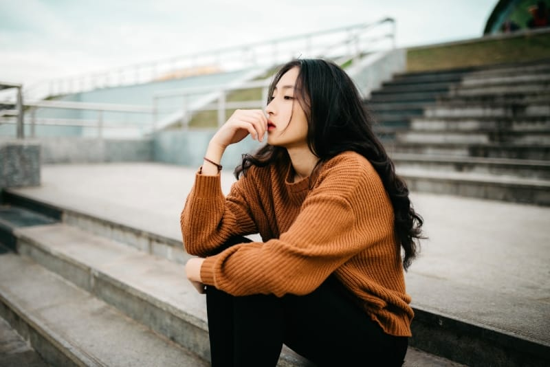woman in brown sweater sitting on stairs