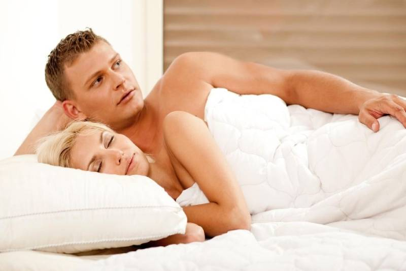 woman sleeping beside a man wide awake thinking