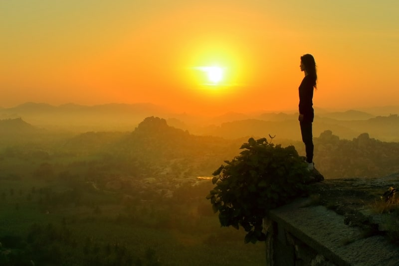 woman standing near cliff during sunset