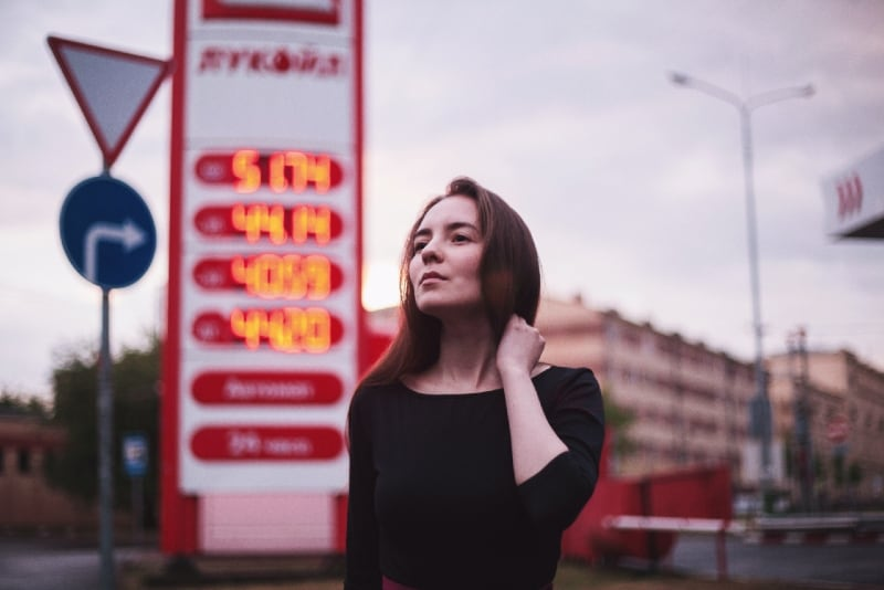 woman in black top standing near gasoline station